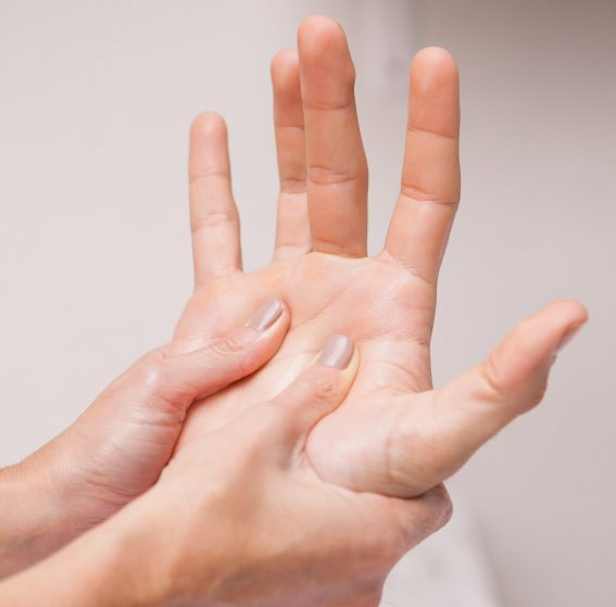 Manicurist massaging a customers hand in a salon
