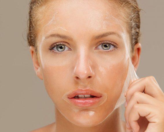 closeup beauty portrait of beautiful blonde woman peeling off a facial mask
