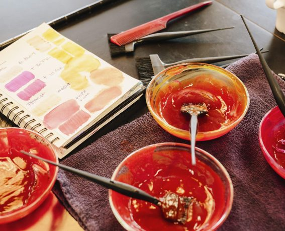 Pots of hair colour and a colour chart in a hair salon.