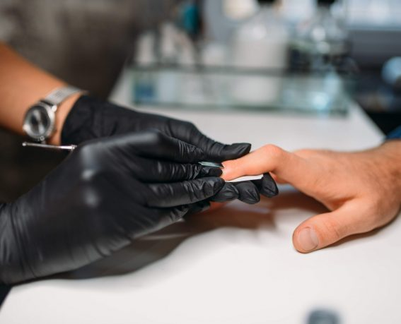 Female master in black gloves polishing nails to male client, top view, men manicure in salon. Manicurist doing hands care procedure