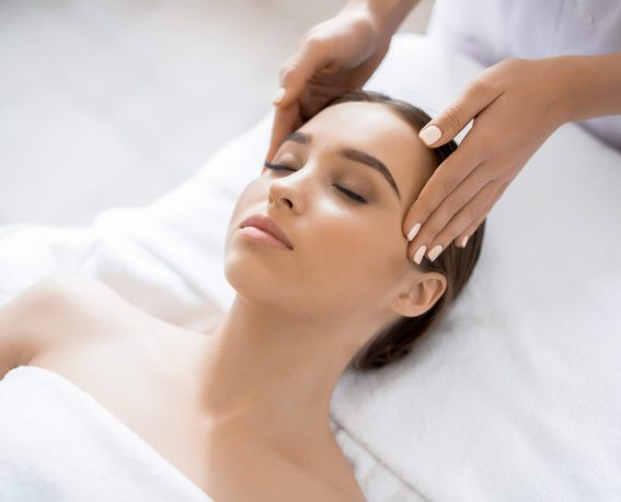 Young woman enjoying spa procedure with her face in luxurious massage salon
