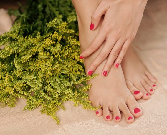 Woman touching soft tender skin of her feet after getting pedicure in spa salon